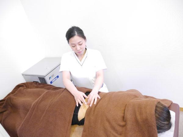 腰に鍼をする女性スタッフ
