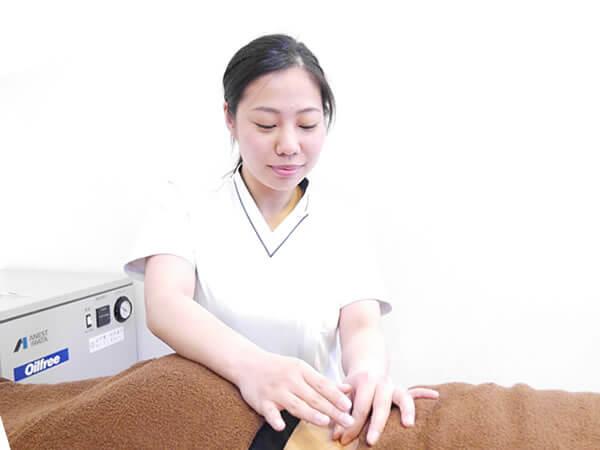 腰痛の人へ鍼施術を行っている女性